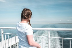 Young pretty girl in sunshine on ferry boat ship deck looking out to sea sailing away from harbour port blue summer skies over English Channel Calais to Dover England