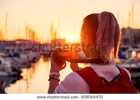 Young pretty girl is taking a picture of a bay with yachts at sunset