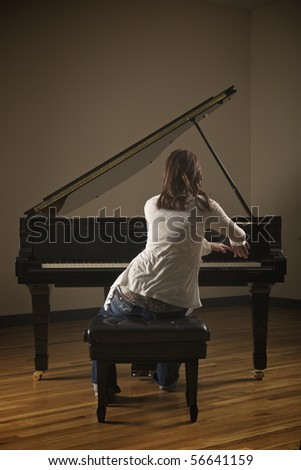 Young pretty girl playing piano in indoor concert hall