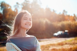 Young pretty girl posing on camera and enjoying sunny autumn day.
