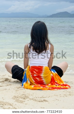 young pretty girl rest at beach with colorful sarong