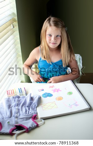 Young pretty girl sitting by window in room drawing colorful images