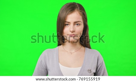 Young pretty girl smiles happily into camera, close up, slow motion over green chroma key screen background stock photo