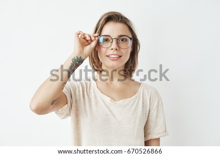 Stock Photo Young pretty girl smiling looking at camera correcting glasses over white background.