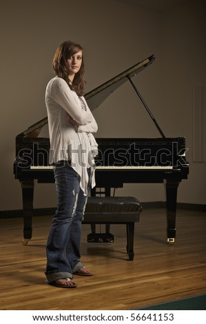 Young pretty girl standing in front of a piano in indoor concert hall