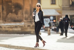 Young pretty girl walk on the street with cup of coffee on her hand and wear sunglasses, sunny day weather