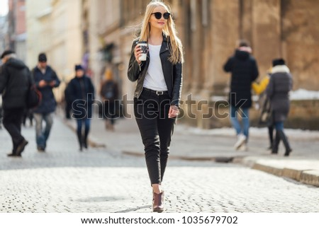 Young pretty girl walk on the street with cup of coffee on her hand and wear sunglasses, sunny day weather #1035679702