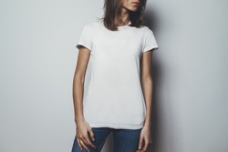 Young pretty girl wearing blank white t-shirt with space for your logo or design, mock-up of white cotton t-shirt, white wall in the background