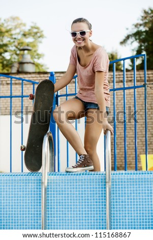 Young pretty girl with snowboard down to the pool, outdoors