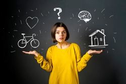 Young pretty girl with symbols drawn around herself such as a heart, brain, bicycle, house. She spread her arms and with a surprised expression thinks about priorities and planning.