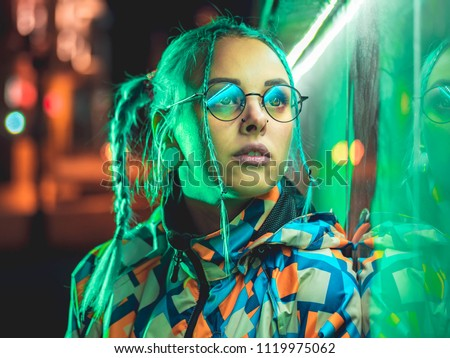 Stock Photo Young pretty girl with unusual hairstyle near glowing green neon light of the city at night. Dyed blue hair in braids. Pensive hipster teenager in glasses.