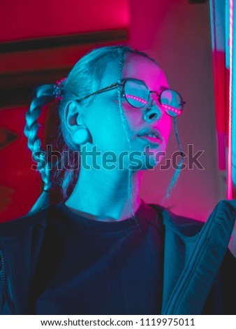 Stock Photo Young pretty girl with unusual hairstyle near glowing pink and blue neon lights of the city at night. Dyed blue hair in braids. Serious hipster teenager in glasses and beautiful lenses.