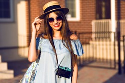 Young pretty hipster cheerful girl posing on the street at sunny day, having fun alone, stylish vintage clothes hat and sunglasses, travel concept , young photographer with vintage camera.