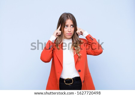 young pretty hispanic woman feeling confused or doubting, concentrating on an idea, thinking hard, looking to copy space on side against blue wall