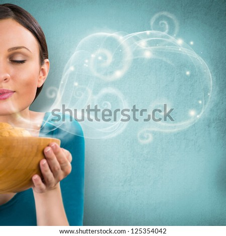 Young pretty housewife holding hot tasty cookies in wooden dish. Graphic smoke flying from dish to copyspace