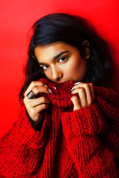 young pretty indian girl in red sweater posing emotional, fashio