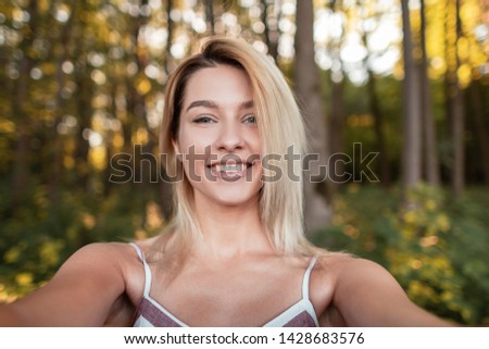 Young pretty joyful woman in a trendy pink dress makes selfie on a phone in the forest among the trees on a summer sunny day.Happy girl relaxes in nature and takes pictures of herself.