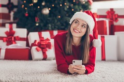 Young pretty lady lay hold cellphone look up white smile wear santa cap red sweater in decorated x-mas living room indoors
