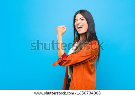 young pretty latin woman feeling happy, satisfied and powerful, flexing fit and muscular biceps, looking strong after the gym against flat wall Stock foto ©