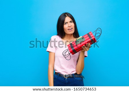 young pretty latin woman feeling puzzled and confused, with a dumb, stunned expression looking at something unexpected against flat wall