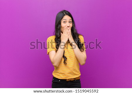 young pretty latin woman happy and excited, surprised and amazed covering mouth with hands, giggling with a cute expression against purple wall