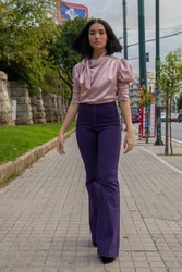 Young pretty model posing in purple long pants in athens greece.