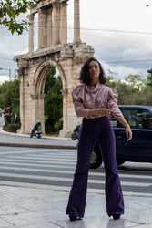 Young pretty model posing in purple outfit outdoors in Athens Greece.