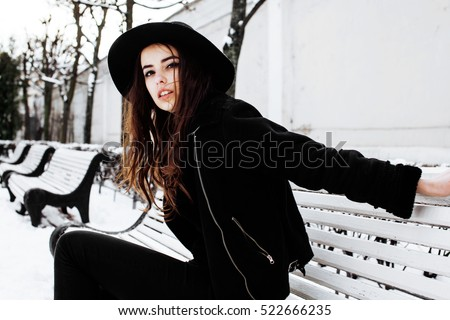 young pretty modern hipster girl waiting on bench at winter snow park alone, lifestyle people concept