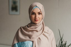 young pretty muslim woman in hijab working on laptop in office room, education online, remote work freelancer, emancipation woman