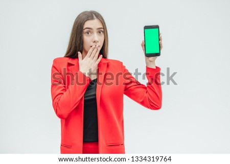 Young pretty pretty girl wearing a red jacket. Stays on a gray background. During this, he holds a black phone in his hand with one hand, the other covers his mouth and bewilderment. #1334319764