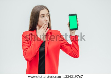 Young pretty pretty girl wearing a red jacket. Stays on a gray background. During this, he holds a black phone in his hand with one hand, the other covers his mouth and bewilderment.