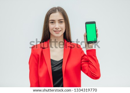 Young pretty pretty girl wearing a red jacket. Stays on a gray background. During this time, holding a black phone with one hand in your hand.
