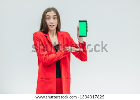 Young pretty pretty girl wearing a red jacket. Stays on a gray background. During this time, holds a black phone. Green screen.