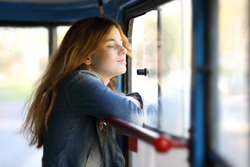 Young pretty red-haired teenage girl dreamily standing at the window facing the wind