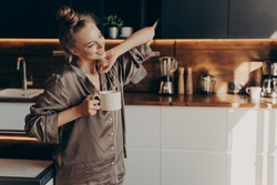 Young pretty relaxed woman in comfy pajama stretching from sleep early in morning while holding cup of coffee in her hand, standing in stylish kitchen interior. Leisure time on average day at home
