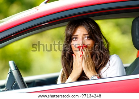 Young pretty scared woman sitting in the red car