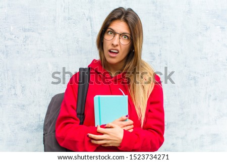 young pretty student feeling puzzled and confused, with a dumb, stunned expression looking at something unexpected