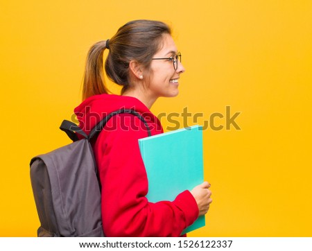 young pretty student on profile view looking to copy space ahead, thinking, imagining or daydreaming #1526122337