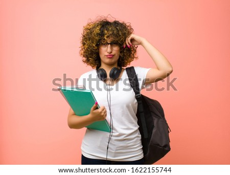 young pretty student woman feeling confused or doubting, concentrating on an idea, thinking hard, looking to copy space on side against pink wall