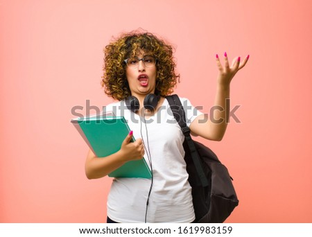 young pretty student woman shrugging with a dumb, crazy, confused, puzzled expression, feeling annoyed and clueless against pink wall
