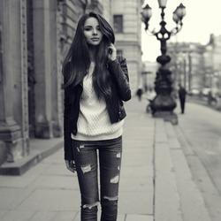 Young pretty stylish girl walking along the street. Monochrome full length portrait