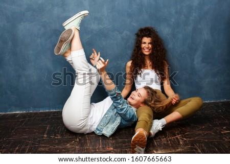 young pretty teenage girls friends with blond and brunette curly hair posing cheerful on blue background, lifestyle people concept