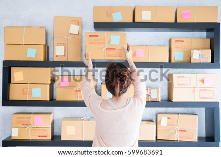 Shutterstock Young pretty teenage work at home write note on parcel box. New generation life style of young entrepreneur
