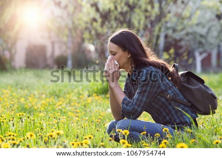 Young pretty woman blowing nose in grassland with spring flowers. Pollen allergy symptoms