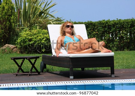 Young pretty woman by the pool of her private villa - stock photo