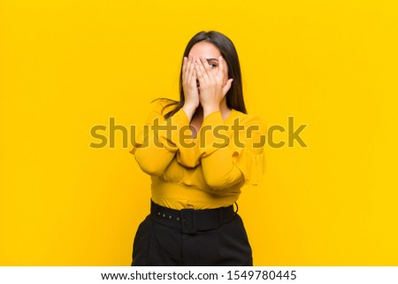 young pretty woman covering face with hands, peeking between fingers with surprised expression and looking to the side isolated against orange wall