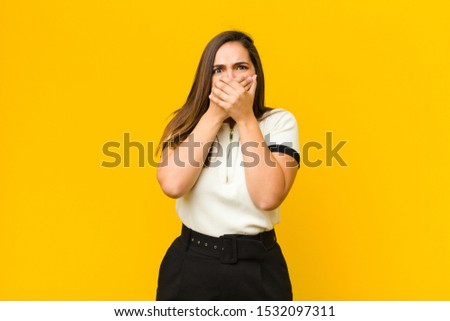 young pretty woman covering mouth with hands with a shocked, surprised expression, keeping a secret or saying oops isolated against orange wall
