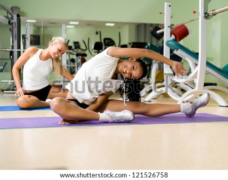 Young pretty woman doing exercises at the fitness club