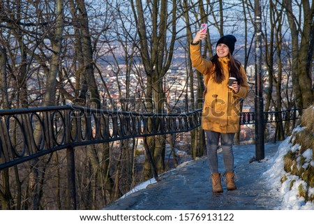 young pretty woman drinking coffee outdoors copy space