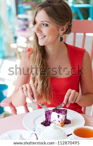 young pretty woman eating tasty cake and smiling